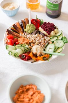 Grande assiette salade végétarienne et vegan : crudités (concombre, tomates cerises, pousses d'épinard) légumes cuits (carottes violettes, mini poivrons saveol, oignons rouges), Riz sauvage et sauces dips vegan : avocat, betterave et tomate séchée - Recette blog cuisine mode lifestyle