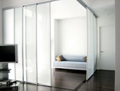 Sliding Door Company- Using frosted glass doors divides a large space without blocking light from the windows.