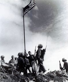 United States Marines from the 5th Division of the 28th Regiment gather around a U.S. flag they raised atop Mt. Suribachi on Iwo Jima during World War II, Feb. 23, 1945. This was the first flag raised by the Marine Corps at Iwo Jima. The raising of a second, larger flag later that day was made famous in the prize-winning photo by Associated Press photographer Joe Rosenthal. Raymond Jacobs claimed that he was the radioman standing at right center in this photograph.