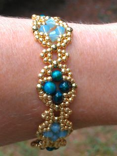 """""""Venetian Band"""" pattern from Deborah Roberti. I used toho 11/0 gold seed beads,3mm gold glass rounds and 4mm swarovski bicones in pacific opal alternating with 4mm sapphire jasper gemstone rounds."""