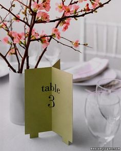 Like a beacon, this table number declares its location in all directions. To make it, use a computer to print numbers onto pieces of colored cover stock (or have numbers calligraphed). Trim the papers to 6 by 7 1/2 inches. For the feet, cut 1/2-inch squares from both corners on bottom edge. Measure over 1 inch for each foot, and mark. Cut out a 3-by-1/2-inch strip between marks. Crease each sheet down the middle, and join the 3 pieces with rubber cement.