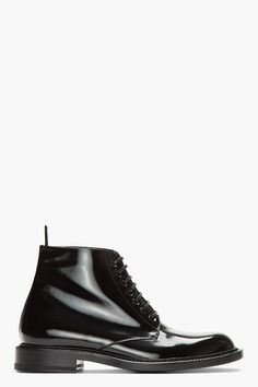 SAINT LAURENT //  Black patent leather combat boots  32418M047007  Ankle-high patent leather boots in black. Almond toe. Tonal lace-up closure. Pull tab at heel collar. Tonal stitching. Tonal sole. Leather. Made in Italy.  $915 CAD