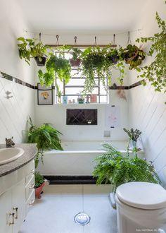 Banheiro tem meia parede revestida com azulejos e varal de plantas em cima da banheira.
