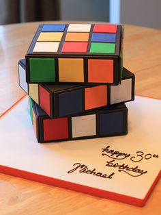 "The 80's seem to be a popular time in our history these days, I see all sorts of 80's themed cakes and party supplies on the web......hmmm, I remember them well! The Rubik's Cube cake was three 6"" single layer cakes, finished with fondant and stacked to look like a turning puzzle. Cookies with the same theme accompanied the cake."