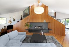 The team took down the solid walls that separated the living room from the adjacent dining room, and opened up sight lines between the living room and the upper floor. #dwell #homerenovation #beforeandafter #seattle