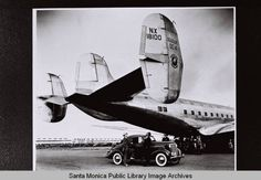 Douglas DC-4 with automobile under the tail of the airplane (NX 18100), ca.1938
