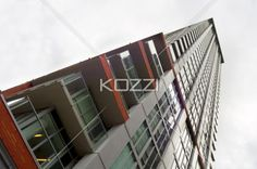 low angle shot of a tall building. - Low angle view of a tall office building against cloudy sky.