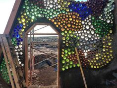 Many brightly coloured bottles hanging in the way. If one of these coloured bottles should accidentally fall. It'll still look awesome! Earthship Design, Earthship Home, Bottle Wall, Natural Building, Outdoor Areas, Roots, Outdoor Living, Glass Art, Awesome