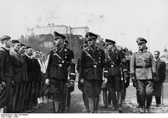 """Reichsführer SS Heinrich Himmler visits Salzburg, Austria and inspects local SS volunteers who haven't worn the uniform yet. On Himmler's left is SS Gruppenfuhrer Karl Wolff, his chief of staff. Austria, as a purely """"Germanic"""" country was considered a prime source for SS manpower."""