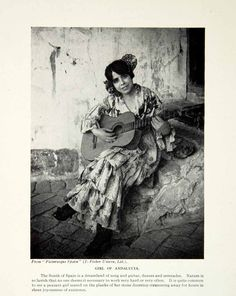 1924 black and white halftone print of a portrait of a Spanish girl playing guitar on the stone steps outside her humble abode in the city of Andalusia, Spain, Europe.