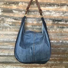 'Double Denim' ... very spacious, casual and comfy shoulder bag with a feature leather like strap held on by brass rings. The exterior is a dark denim gusset and a nicely contrasting lighter denim front and back panel. The interior is fully lined and has a slip pocket and a zip