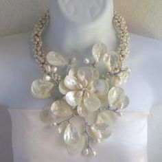 @Overstock.com - Sterling Silver Pearl and Mother of Pearl Colossal Floral Necklace (Thailand) - This colossal necklace features mother of pearl in an eye-catching floral design on the front, with white freshwater pearls along the back. The necklace is handmade of sterling silver by artisans in Thailand.  http://www.overstock.com/Worldstock-Fair-Trade/Sterling-Silver-Pearl-and-Mother-of-Pearl-Colossal-Floral-Necklace-Thailand/5096703/product.html?CID=214117 $99.99