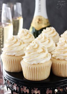 These champagne cupcakes are guaranteed to be the star of your dessert table! Decorate the moist and delicious cupcakes with vanilla frosting, and add gold sprinkles for an extra sparkle. Photo credit: Life, Love and Sugar New Year's Desserts, Delicious Desserts, Yummy Food, Plated Desserts, Delicious Cupcakes, Cupcake Recipes, Cupcake Cakes, Dessert Recipes, Cupcake Emoji