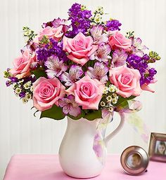Make Their Day ™ Bouquet  It's their day. Make them smile beyond a doubt with a brilliant arrangement of pink roses, purple stock, alstroemeria, monte casino and salal. Hand-designed in a stylish, white ceramic pitcher they can reuse later to serve their own smiles.