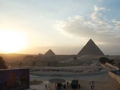 day tour pyramids cairo- WWW.egypttravel.cc sunset tour on the pyramids with the great sphinx looking to sun between two pyramids with Egyptian land .