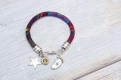 Pulsera de cordón étnico con colgantes en forma de estrella, swarovski y pie grabado con una inicial.