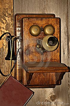 Old fashioned telephone hanging on wall with phone book attached by string.