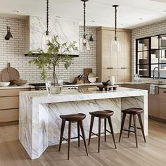 Light wood, white range hood, wood cabinets marble island top and sides, modern dark wood stools, white subway tile dark grout. Nam Dang Mitchell