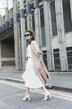 Sara Escudero is wearing a long cream dress, nude maxi coat and matching boots