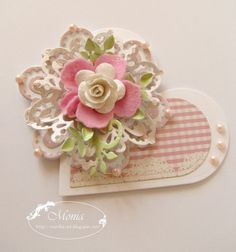 Paper flower on heart...would be a cute embellisment on a valentine or wedding card.  Is that a snowflake for the underpart of the floiwer that looks like a mini doily?