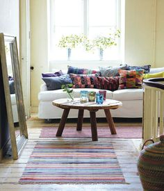 i like the rustic coffee table and the large mirror leaning against the wall