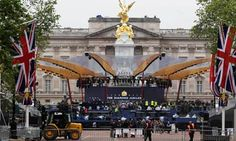 Workers prepare the stage for the diamond jubilee concert in front of Buckingham Palace. The Queen will light the last of more than 4,200 beacons when the performances have finished. Photograph: David Moir/Reuters