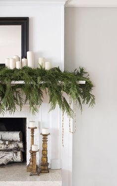 I love how free and natural this mantle greenery looks. The simple white candles… I love how free and natural this mantle greenery looks. The simple white candles layered into the greenery create a simple and laidback Christmas look. Diy Christmas Fireplace, Christmas Mantels, Noel Christmas, Vintage Christmas, Ikea Christmas Tree, Rustic Christmas, Christmas Sangria, Christmas Cards, Christmas Quotes