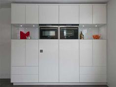 Moderne maatwerk keuken met glazen blokken als opbergvakken.