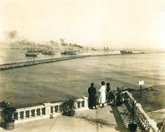 Three women look out at ships in LA Harbor, circa 1919. Image appears to be taken from the Point Fermin Bluffs, just south of the Breakwater.Historic Photographs Collection.