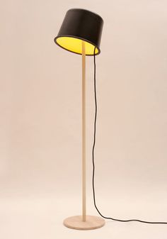 "nspired by Charlie Chaplin's trademark hat and walking stick, Martin Hirth created the Chaplin Lamp. Made of a simple wooden stand and metal lampshade, the fixture's ""hat"" is easily adjustable allowing it to sit at different angles."