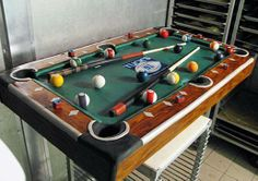 """Billiards Cake made of red velvet cake, cream cheese filling, buttercream, fondant (pool balls, green """"felt""""), cereal treats (pool table bumper). Piping gel was used to achieve the wood grain look. What's memorable about the cake? This cake looked so much like a real billiards table complete with balls, cues and even chalk...and everything was edible. Buddy put letters on the balls instead of numbers as a nod to the literacy theme of the event."""