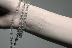 White ink snowflake tattoo.