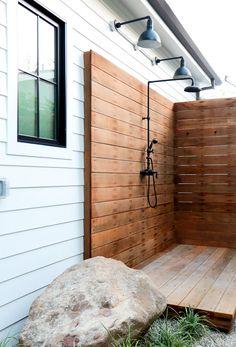 Outdoor wooden shower and black light fixtures