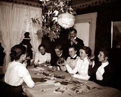 Orville Wright at Dinner Party Here we present a dramatic image of Orville Wright and group around a table, looking at photographs, during a party at 7 Hawthorn Street. It was taken in 1899.  The image was taken by Wilbur Wright.