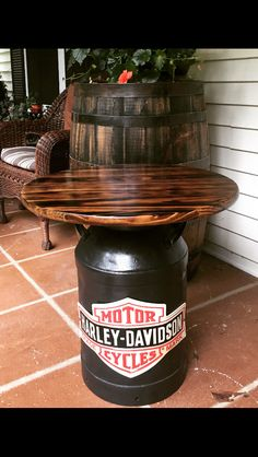 Harley Davidson table I made using an old milk can. I sanded the milk can and sprayed it with a rust inhibitor. I spray painted the can with Hammered spray paint. I then added the tin Harley sign. I bought a precut wood round piece at a box store. I torched it and then stained and poly-ed it. Attached it to the can and now it's for sale in our store, Lynthia Designs.