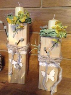Holzpfosten, dekoriert mit Blüten, Kränzchen und Kerzen