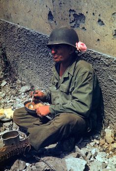 Time for chow: GI rests against a wall to have lunch en route to Rome, Italy, 1944. There's some kind of stew, bread, cake (?) and a good amount of coffee - a far better menu than the one available to the retreating Germans. Note the rose worn on the helmet.