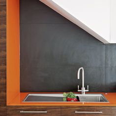 Clearly not a Halloween kitchen nightmare! That glowing orange worktop, sandwiched between a matt-black tiled wall and zebrano wood cabinetry, all finished with minimal stainless steel hardware... It's breathtaking, in a very good way.