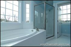 Cantilever (an alcove with no foundation underneath) tub with white custom tile surround. Glass enclosed shower. Light blue paint.