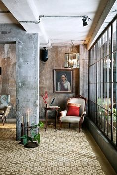 Elegant antique art and furniture are a stunning contrast to this exposed concrete room, where a wall of paned windows looks into the adjoining space. A patterned tile floor softens the room...