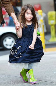 Only Suri can make a navy blue tulle-lined party dress and green boot combo look good.