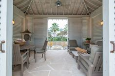 Barber designed thepool house cabana's sliding shutter doors to allow an easy breeze and views to the outdoor fire pit. The faux bois antique birdhouse in the corner was inspired by the home's proximity to the bird sanctuary and adds an element of whimsy to the space.