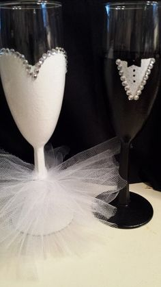 Cute bride and groom decorated champagne flutes make a perfect  gift for the wedding toast.  Bride glass is painted white with silver rhinestones along top of dress with tulle netting along the stem like a dress. The tulle is removable for washing.  The groom glass is painted black with white shirt,