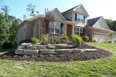 Backyard landscaped bed with natural stone retaining walls built by H Landscaping.