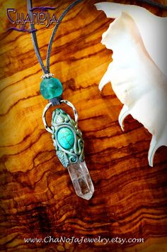 "Crystal Jewelry Aqua Soul Mermaid Pendant-enchanted necklace turquoise swarovski crystal quartz point pure beauty divine feminine ocean love by chanoja jewelry. ts name is ""Aqua Soul"" and it is created in beautiful light grey and ivory tones. The pendulum features a gorgeous transparent crystal quartz point and a beautiful turquoise howlite. To give it a touch of magic, I included a sparkly swarovski crystal, applied different paints and iridescent fairy dust."