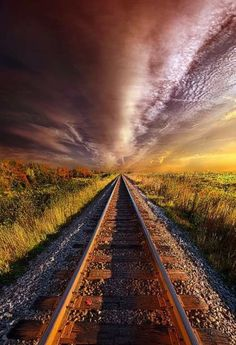 This image uses perspective and symmetry to give it's effect. The train tracks seem to stretch out infinitely to the vanishing point, as well as the sky and grass around it. The photograph is taken somewhere around sunrise / sunset giving it a warm, rustic tone. The colours of the sky stand out from the ground, but don't clash. The train tracks and the storm could suggest a long journey.