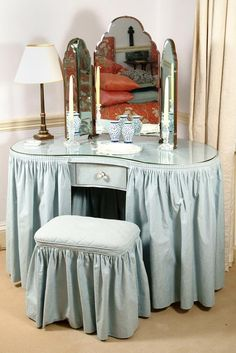A blue cotton covered kidney shaped dressing table with tri-fold mirror--tres elegant!