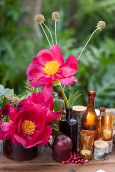 Eclectic mix of bottles and stems of fowers | via TheELD.com