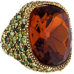 Gold-tone Kenneth Jay Lane cocktail ring featuring orange crystal center with green crystal embellishments throughout shank.