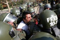 A student protester bites a riot policeman while being detained during a riot at a rally demanding Chile's government reform the education system in Santiago, May 8, 2013.  Read more: 2013: The Year in Global Protest   TIME.com http://world.time.com/2013/12/19/the-year-in-protest-2013/#ixzz2rNbnmPKI
